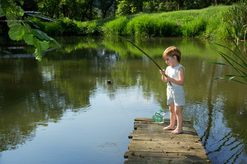 Little Boy Fishing from Wooden Dock and Waiting for his Catch