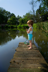 Little Boy Standing on Wooden Dock and Fishing on  Lake