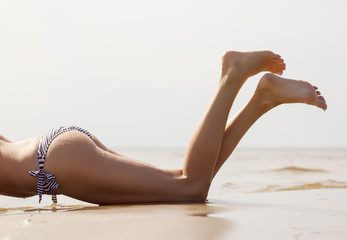 Beautifully tanned woman's legs on the beach