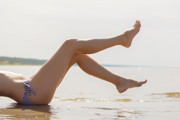 Beautiful woman's legs on the beach