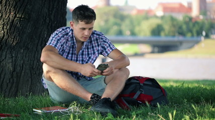 Young student with smartphone sitting on grass in city park