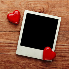 Photo frame and small red hearts on old wood background,
