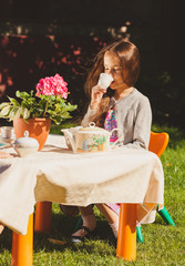 cute girl drinking tea at toy table at yard