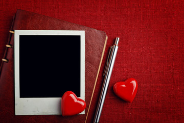 Notebook, photo and hearts on fabric background