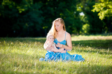 Young beautiful happy woman with a child in the meadow