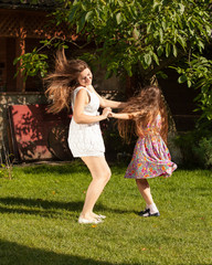mother and daughter dancing on grass at sunny day
