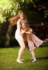 young mother and daughter dancing on grass at yard