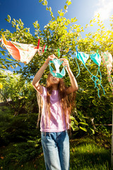 girl hanging clothes with clothespins at sunny day