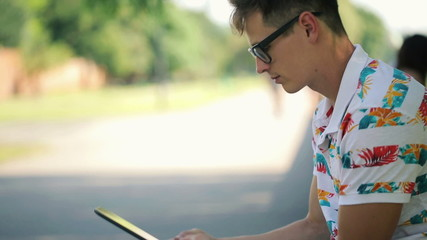 Young trendy man with tablet computer in the city