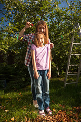 mother hanging daughter on string with clothespin