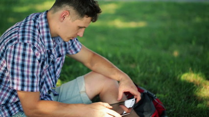Young student with tablet computer sit on grass in the park