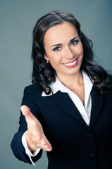 Businesswoman giving hand for handshake, over grey