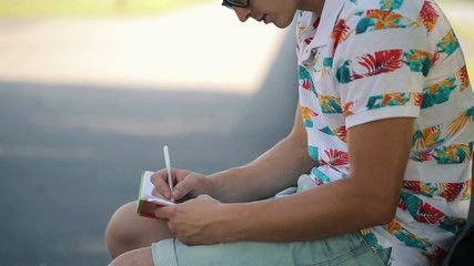 Young man writing in notebook in city park