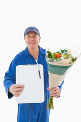 Happy flower delivery man showing clipboard
