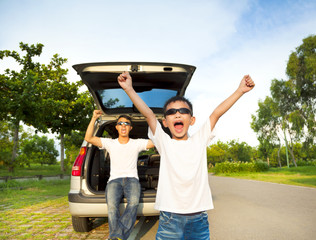 happy children and father raise arms with their car