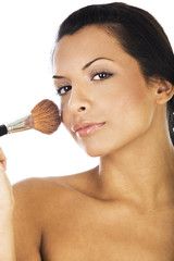 Beautiful young woman applying  blush with makeup brush