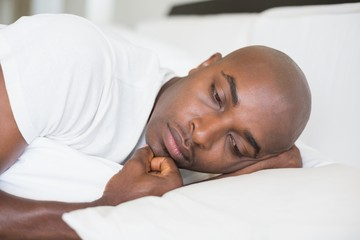 Unhappy man lying in bed