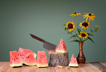 Cutted ​​watermelon and flowers in metal vase