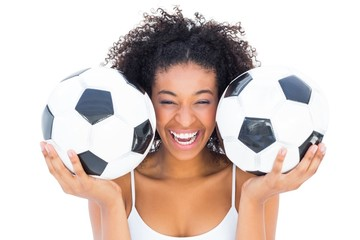 Pretty girl holding footballs and laughing at camera
