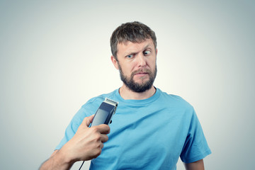 Funny bearded man with a hair-clipper