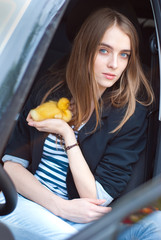 beautiful girl sitting in the car and keeps the duckling
