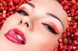 sensual woman licking lips lying in wild strawberries