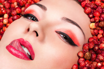 sensual woman licking lips lying in wild strawberries