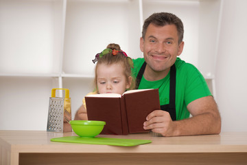 Family concept, cute little girl with father preparing to cook
