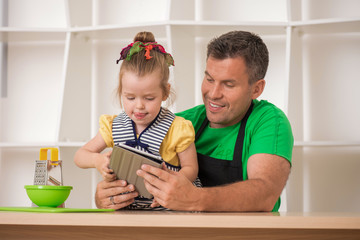 Handsome father and cute little daughter cooking with tablet