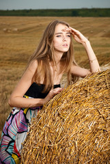 beautiful young girl stands near haystack of hay in the field
