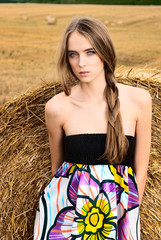 girl in a field with haystacks