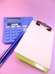 電卓とペンとバインダーに挟まったメモ用紙