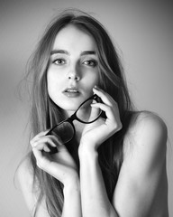 black and white portrait of beautiful girl with glasses in hands