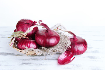Fresh red onions in wicker basket