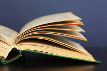 Opened book on wooden table on color background
