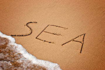 sea handwritten in sand on a beach