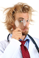 Funny doctor in glasses holding magnifier close up
