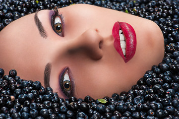 Beauty Fashion woman face in blueberries