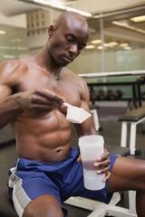 Body builder scooping up protein powder