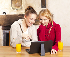 Two beautiful women work on the tablet