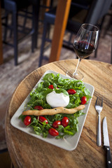 Mozzarella, tomato and green salad on a plate