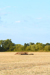 Harrow among the stubble on harvested farmland