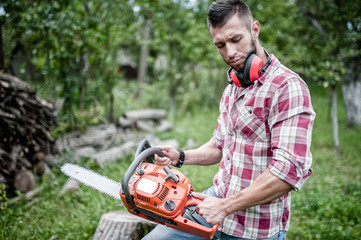 portrait of sexy and hansome man with chainsaw