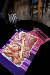 Ham, sausage and bacon on a plate, glass of wine