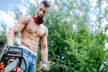 portrait of agressive athletic man with chainsaw getting ready