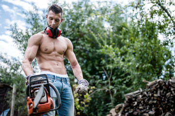 portrait of sexy man with chainsaw and protective gear ready