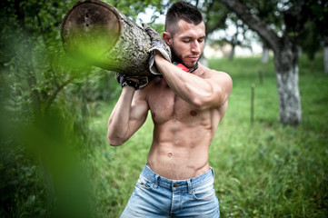 male model carrying and cutting wood logs for firewood
