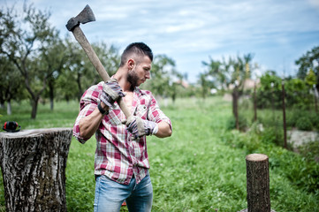 athletic male lumberjack cutting logs for firewood with axe