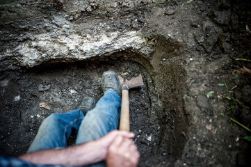 man with shovel and spade working and digging a hole in ground
