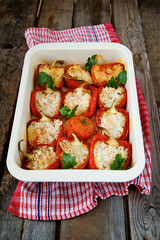 Red peppers stuffed with rice in a baking dish